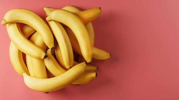 Świeże kiść żółtych bananów na białym tle na różowym tle.