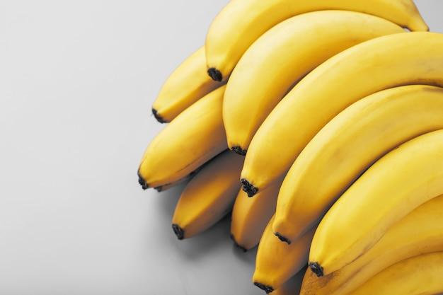 Świeże kiść żółtych bananów na szarym tle
