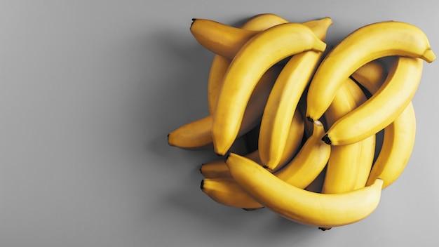 Świeże kiść żółtych bananów samodzielnie na powierzchni gray