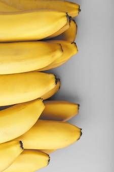 Świeże kiść żółtych bananów samodzielnie na szarym tle