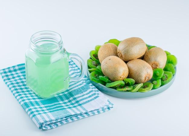 Świeże kiwi w talerzu z suszonych kiwi, pić wysoki kąt widzenia na piknik szmatką i białym tle