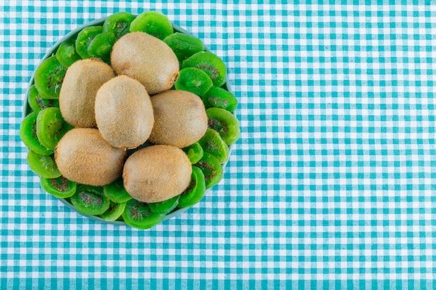 Świeże kiwi w talerzu z suszonym kiwi mieszkanie leżało na tle tkaniny piknikowej