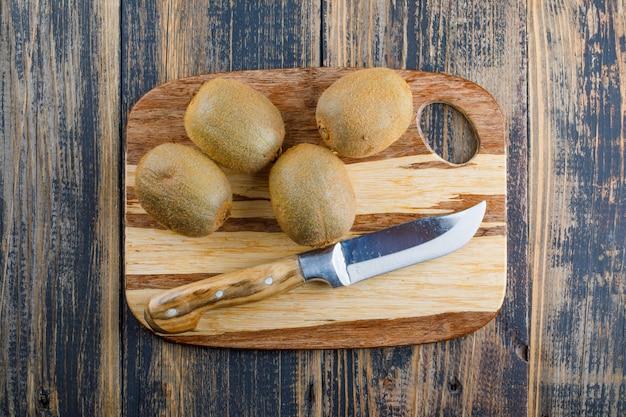 Świeże kiwi z płaskim nożem leżał na tle drewniane i deska do krojenia