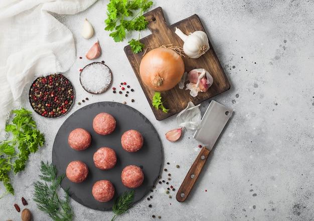 Świeże klopsiki wołowe na kamiennej desce z pieprzem, solą i czosnkiem na jasnej powierzchni z koperkiem, pietruszką i koperkiem i cebulą. widok z góry