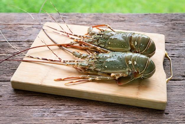 Świeże kolczaste homary w drewnianym talerzu na drewnianym stole w tle świeże kolczaste homary owoce morza