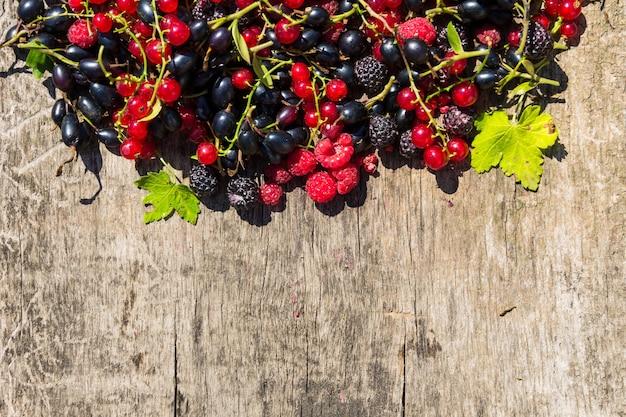 Świeże kolorowe jagody na drewnianym tle. jeżyny, maliny, czerwone i czarne porzeczki na stole. zdrowe odżywianie i dieta koncepcja. widok z góry z miejscem na kopię