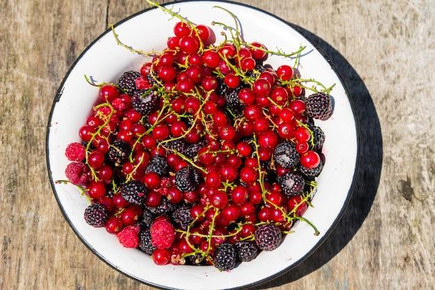 Świeże kolorowe jagody na drewnianym tle. jeżyny, maliny, czerwone i czarne porzeczki w misce na rustykalnym stole. zdrowe odżywianie i dieta koncepcja. widok z góry