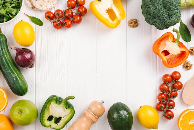 Świeże kolorowe warzywa; owoce i pieprzniczki na białym drewnianym biurku