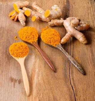 Świeże korzenie kurkumy z kurkumą w proszku na drewnianym stole
