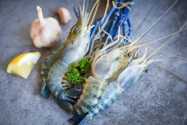 Świeże krewetki krewetkowe z przyprawami czosnek cytrynowy do gotowania na ciemnym tle w restauracji z owocami morza - surowe krewetki