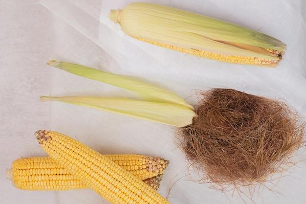 Świeże kukurydze na kolbach na białym stole.