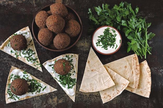 Świeże kulki falafel, pita, sos i zioła. falafel wegański. zdrowe, chude jedzenie. kuchnia bliskowschodnia.