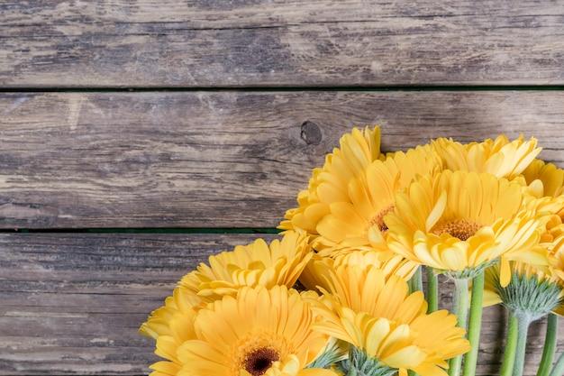 Świeże kwiaty gerbera na drewnianym tle