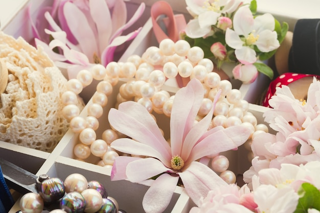 Świeże kwiaty jabłoni i magnolii z perłami i koronką vintage