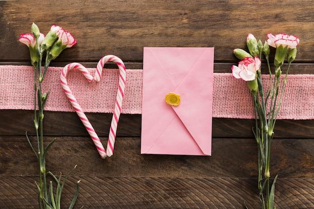 Świeże kwiaty w pobliżu wstążki, koperty i cukierki laski
