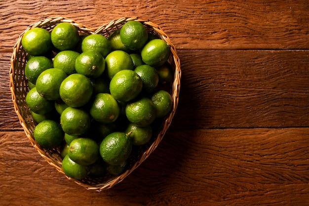 Świeże limonki w misce serca na tle drewniany stół. widok z góry.