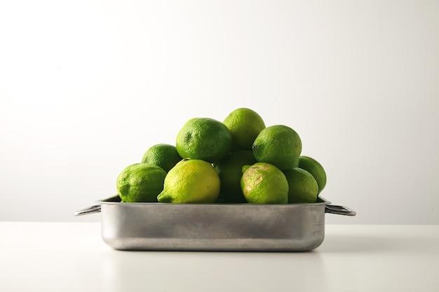 Świeże limonki w stalowym rondlu na białym stole.