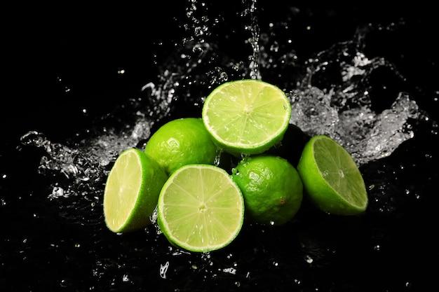 Świeże limonki z bryzgami wody w ciemności