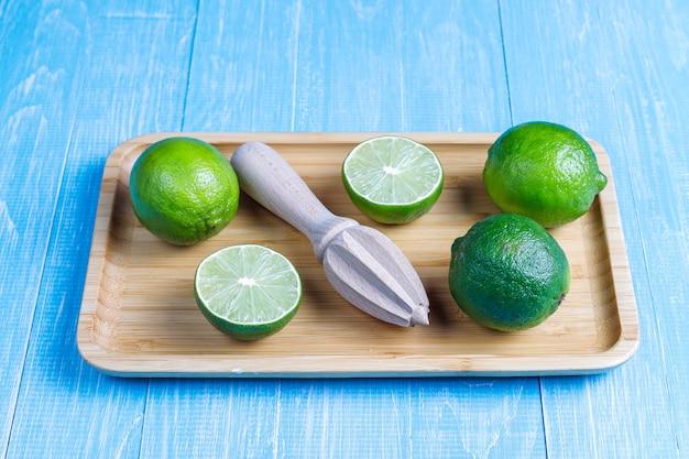 Świeże limonki z drewnianą sokowirówką cytrusową