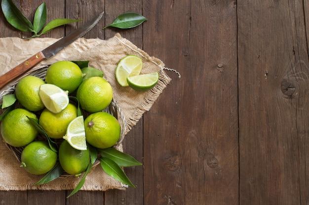 Świeże limonki z nożem i liśćmi na drewnianym stole widok z góry z miejsca na kopię
