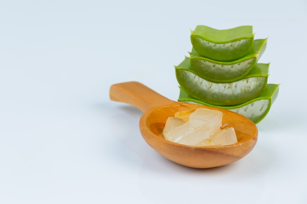 Świeże liście aloe vera z plastrami i żelem na drewnianej łyżce. aloe vera to naturalne zastosowanie ziół dla urody.