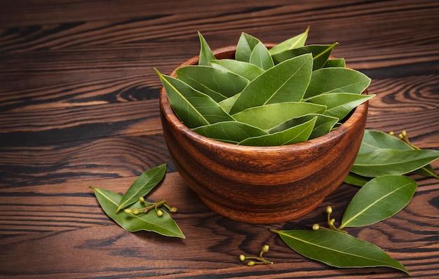 Świeże liście laurowe w drewnianej misce na ciemnym tle rustykalnym