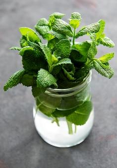 Świeże liście mięty w małym szklanym słoiku