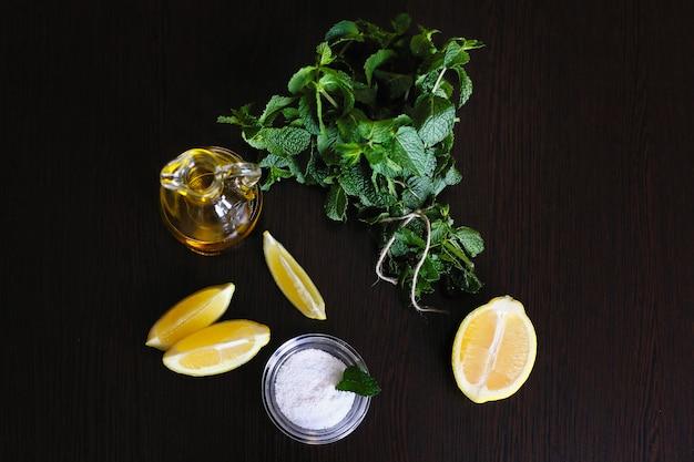 Świeże liście mięty w moździerzu na stole, zioła i przyprawy, cytryny i oliwa z oliwek na drewnianym stole.