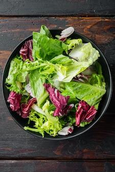 Świeże liście różnych sałatek, na starym ciemnym tle drewnianego stołu, widok z góry płaski lay