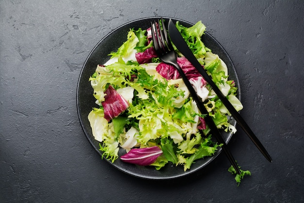 Świeże liście różnych sałatek na talerzu ceramicznym