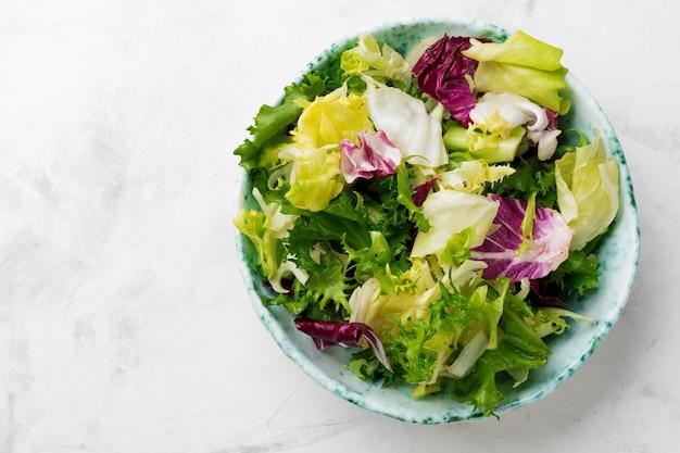 Świeże liście różnych sałatek w talerzu ceramicznym