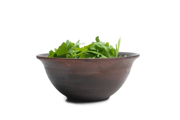Świeże liście rukoli w ceramicznej misce brązowy na białym tle.