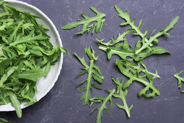 Świeże liście rukoli w misce na ciemnym stole. świeże wegetariańskie jedzenie koncepcja, zbliżenie, płaskie lay