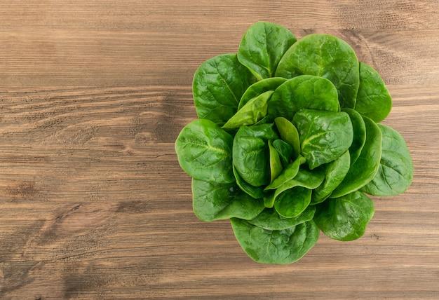 Świeże liście szpinaku dla dzieci. spinacia oleracea na drewnianym tle. liściaste zielone warzywa widok z góry