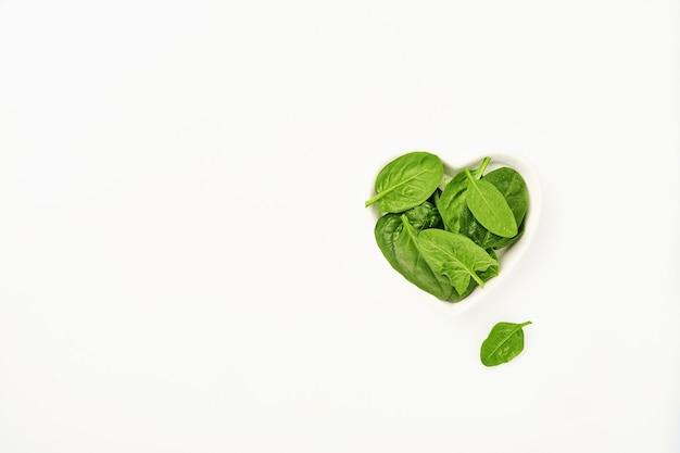 Świeże liście szpinaku w misce w kształcie serca na białym tle, na białym tle.