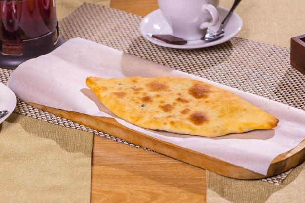Świeże lobiani i chaczapuri na drewnianym stole w ekologicznym opakowaniu. tradycyjne gruzińskie wypieki i jedzenie.