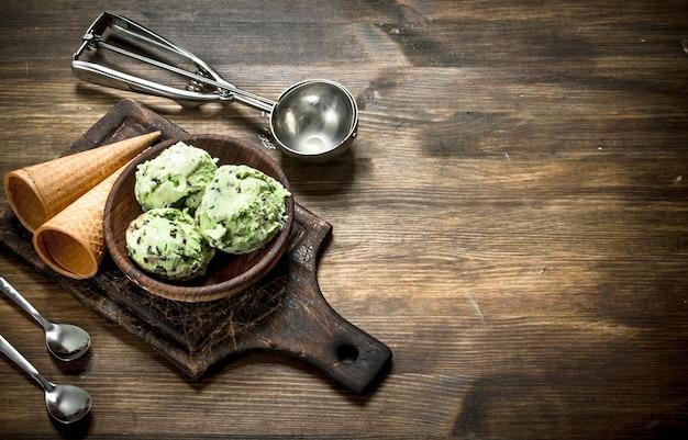 Świeże lody pistacjowe w misce z kubkami waflowymi na drewnianym stole