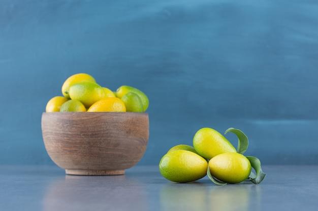 Świeże małe mandarynki w drewnianej misce.