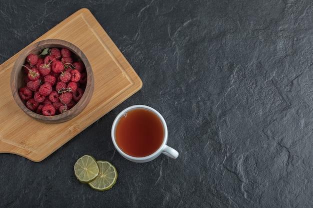 Świeże maliny na drewnianej desce z herbatą i cytryną.