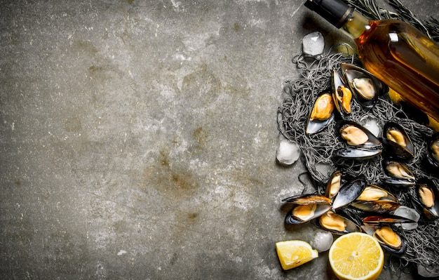 Świeże małże na sieci rybackiej z cytryną i winem. na kamiennym stole. wolne miejsce na tekst. widok z góry