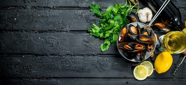 Świeże małże z owoców morza z białym winem i pietruszką. na czarnym tle rustykalnym.