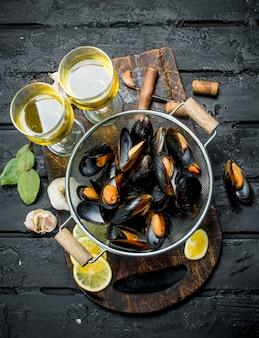 Świeże małże z owoców morza z białym winem. na czarnej powierzchni rustykalnej.