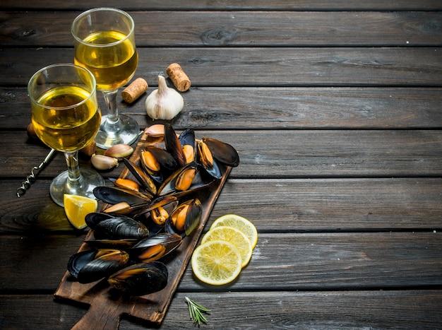 Świeże małże z owoców morza z cytryną i białym winem. na drewnianym tle.