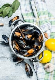 Świeże małże z owoców morza z cytryną. na rustykalnym tle.