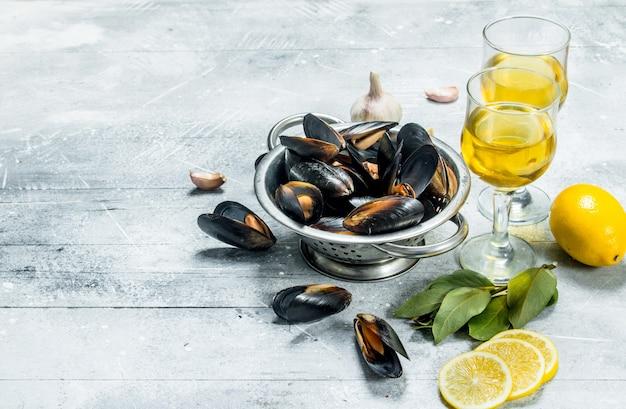 Świeże małże z owoców morza z kawałkami wina i cytryny. na rustykalnym tle.