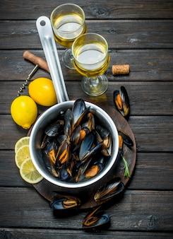 Świeże małże z owoców morza z kieliszkami białego wina. na drewnianym.