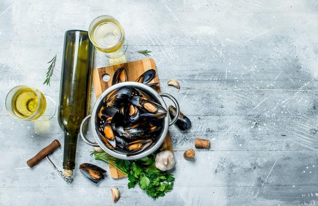 Świeże małże z owoców morza z pietruszką i białym winem. na rustykalnym stole.
