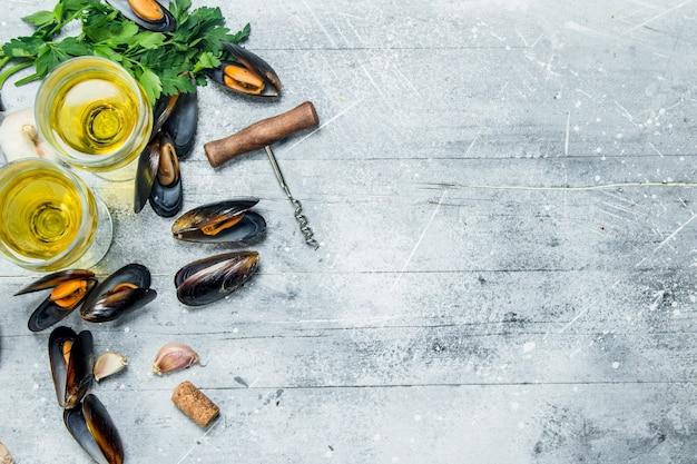 Świeże małże z owoców morza z pietruszką i białym winem na rustykalnym stole.