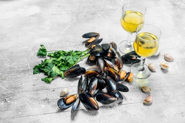 Świeże małże z owoców morza z pietruszką i białym winem. na rustykalnym tle.