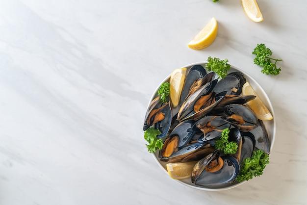 Świeże małże z ziołami w misce z cytryną